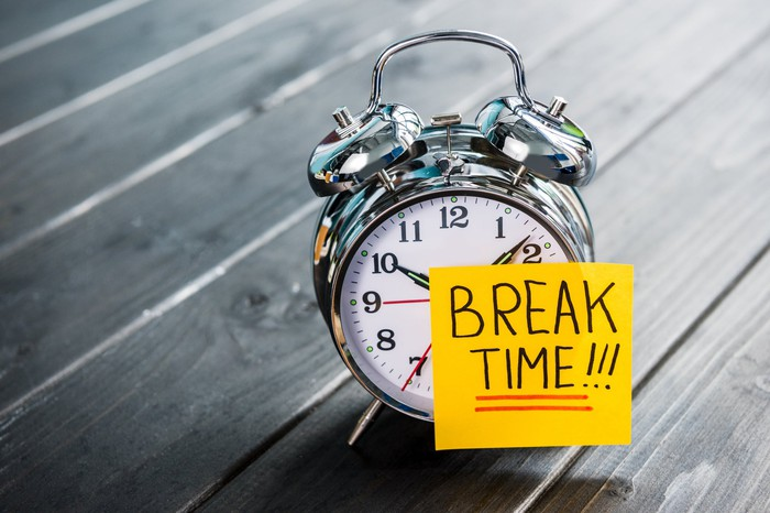 """An alarm clock bearing a sticky note on which is written """"Break time!"""""""