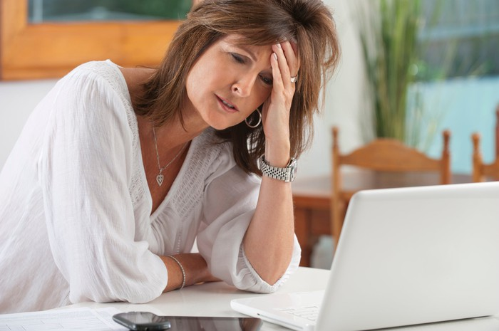 A worried-looking woman sitting in front of an open laptop with her left hand on her forehead.