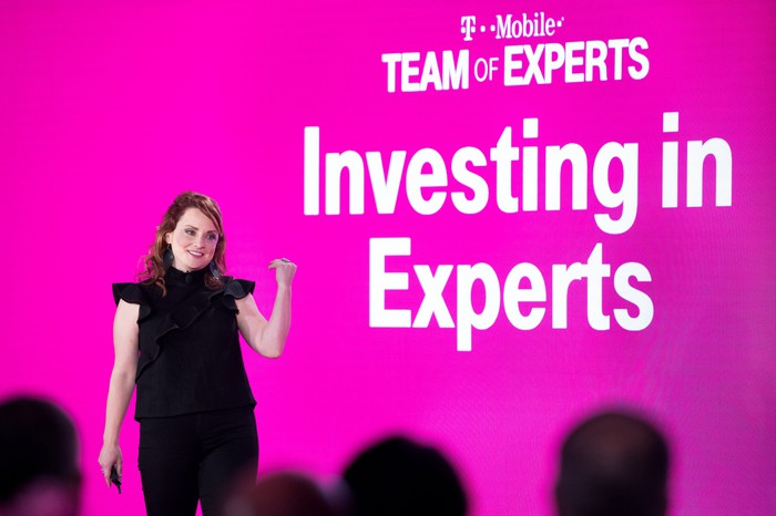 T-Mobile Executive Vice President of Customer Care Callie Field standing in front of a screen that says Investing in Experts.