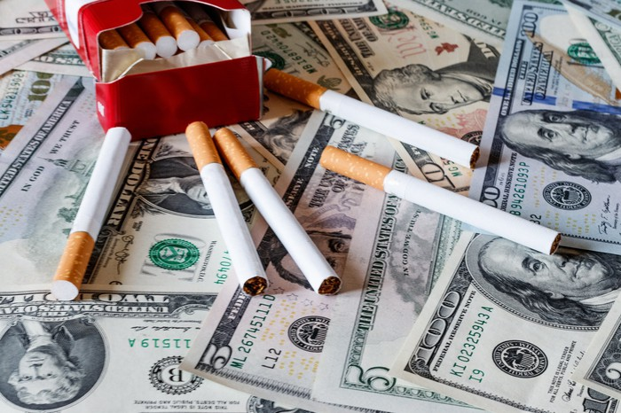 Cigarettes in a red box, some spilling out on a pile of cash.