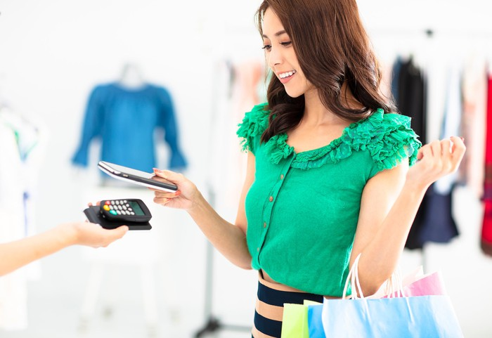 A young woman pays for clothes with a smartphone.