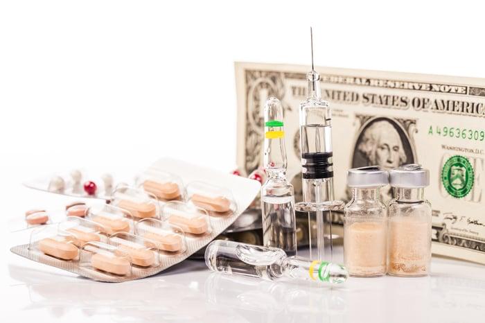Pills, syringe, vaccine bottles, and a dollar bill.