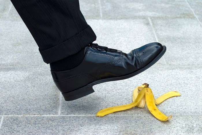 A black shoe about to step on a banana peel.