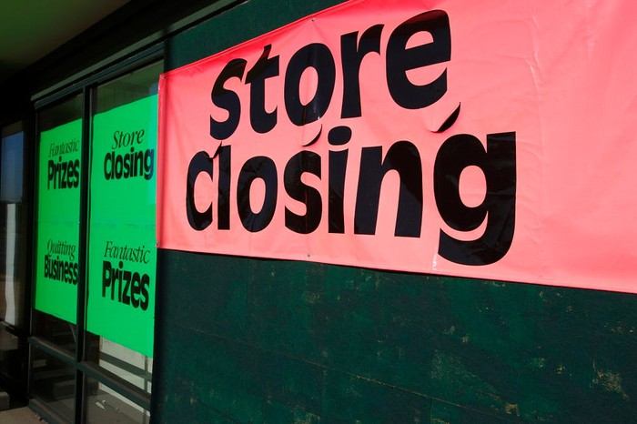 Green and red store closing signs on storefront.