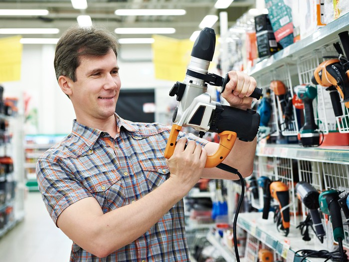 A customer holds a power drill in a home improvement store.