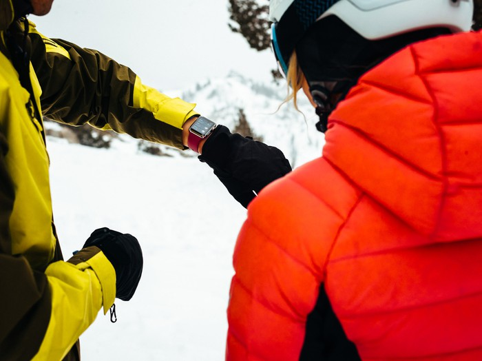 A skier looking at an Apple Watch