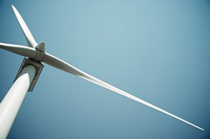 A wind turbine viewed from directly below the rotors.