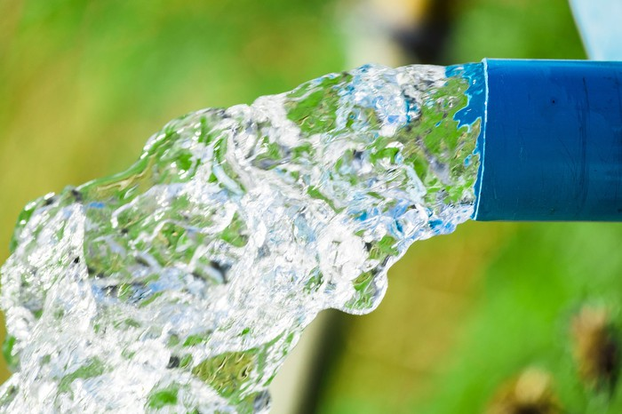 Water flowing out of a blue pipe or hose with greenery in background.
