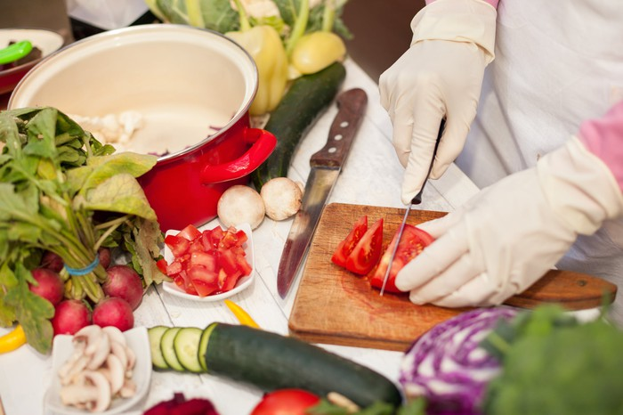 A woman cuts fresh produce.