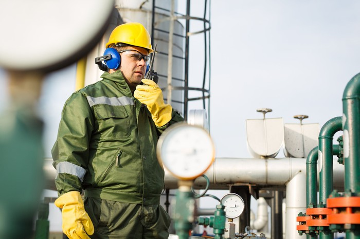 A man talking on a communications device in front of midstream infrastructure