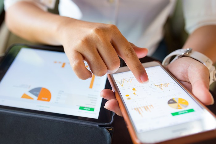 Person holding smartphone and tablet displaying charts.