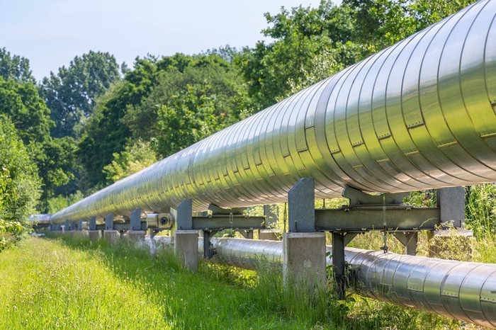 A natural gas pipeline running through a green forest.
