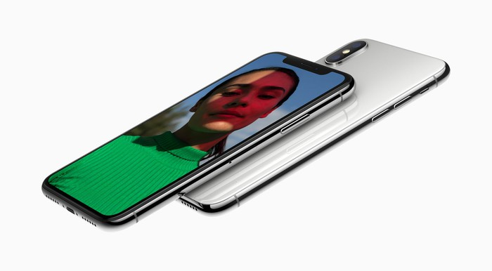 One Apple iPhone X faceup and pointing to the left with another iPhone X, this time face down, underneath it.