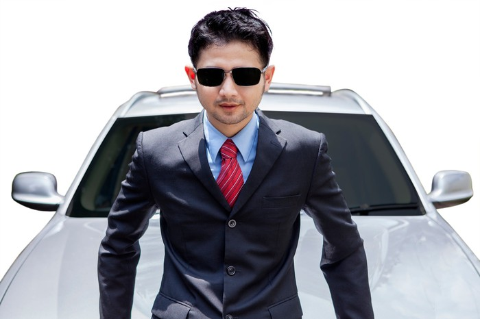 An Asian man in a suit and sunglasses is sitting on the hood of a car.