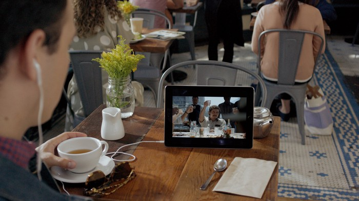 A person streaming Netflix on a tablet in a cafe.