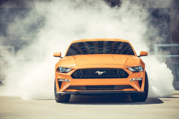 Orange Mustang with smoke coming from rear tires