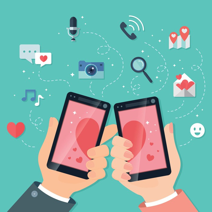 An illustration of two smartphones displaying two halves of a heart.