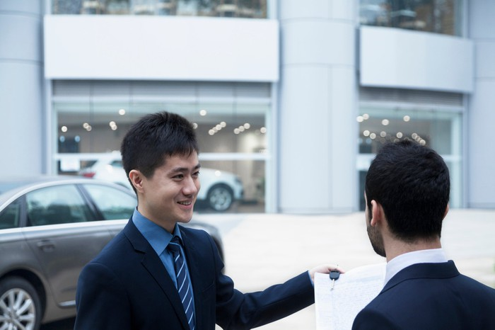Car salesman holding car keys and paperwork and selling a car to a young businessman