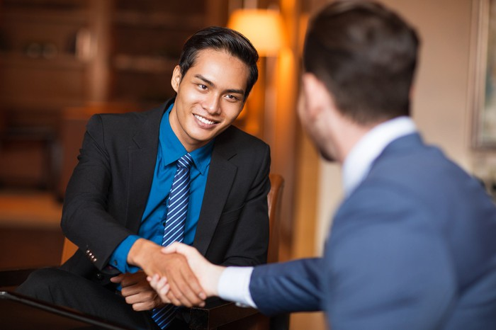 Two men in business suits shake hands.