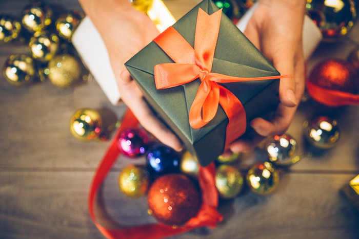 Hands holding out a small gift wrapped in a bow with Christmas decorations on the floor.