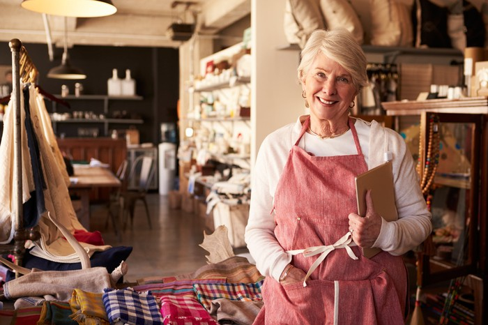 Senior woman in apron holding a notebook