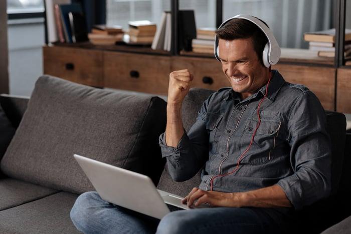 A man wearing headphones cheers as he looks at his laptop.