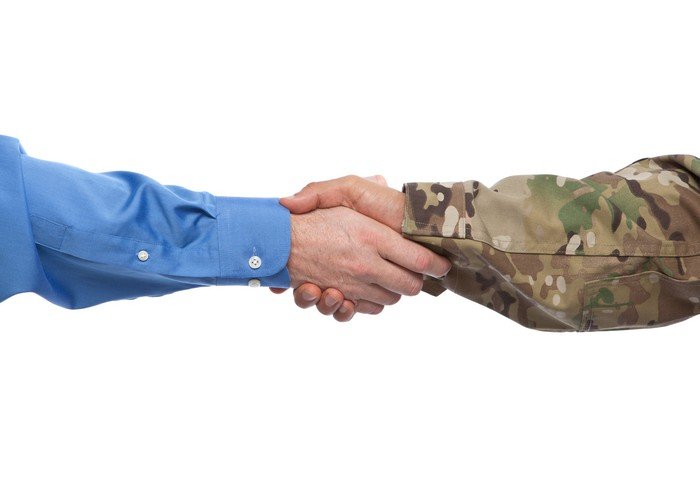 A picture of two hands shaking; one arm is in a blue shirt, one is in military camouflage.