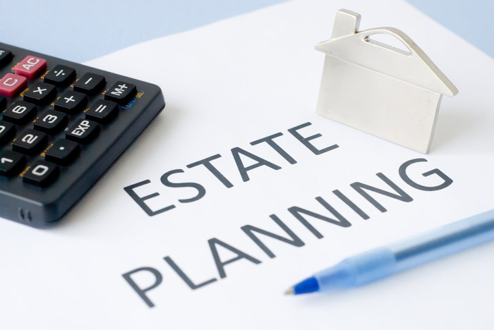 Paper marked Estate Planning on a blue surface, with a calculator, pen, and house icon on top of it.