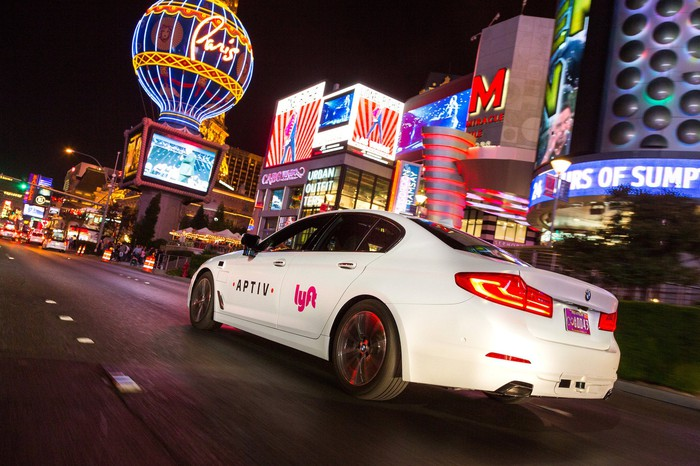 A white BMW with Aptiv and Lyft logos is shown on a Las Vegas street at night.