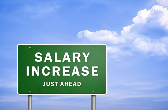 "A green sign that says ""salary increase just ahead"" in front of blue skies."