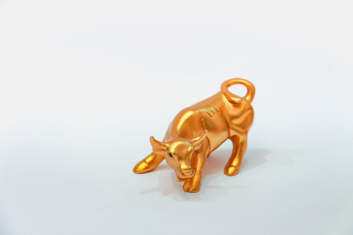 Tiny golden bull figurine in an aggressive pose on a plain white table.