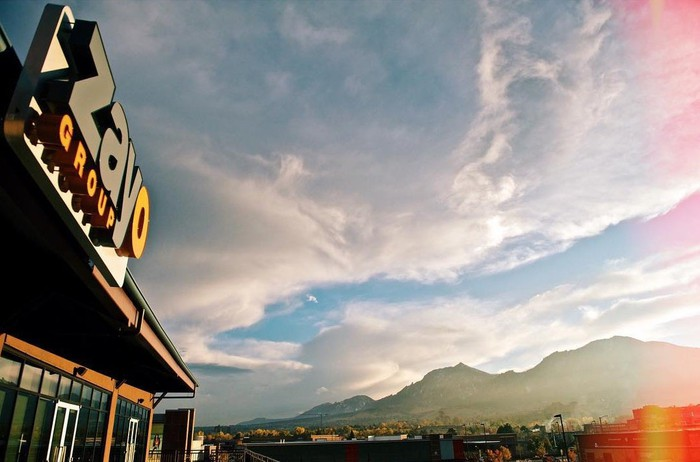 Storefront with Zayo sign on top in front of a mountain landscape.