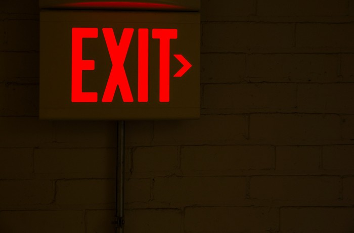 An illuminated exit sign on a wall in a dark room.