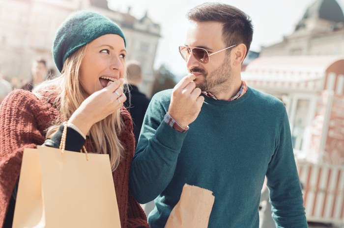 A woman and a man snack on something in a paper bag while walking outdoors.