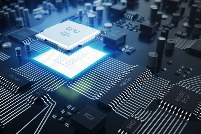 """A computer chip with the letters """"CPU"""" hovering a motherboard."""