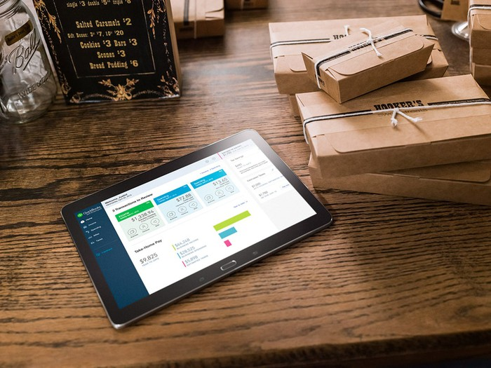 QuickBooks Online on a tablet that's sitting atop a wooden table and alongside boxes wrapped with brown paper.