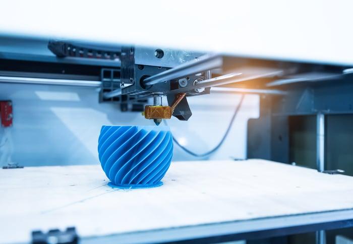A 3D printer printing a blue vase.