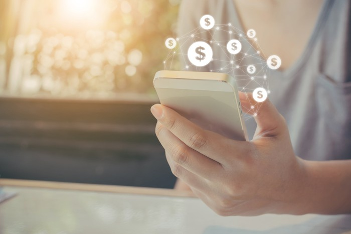 Dollar signs rising out of a smartphone.