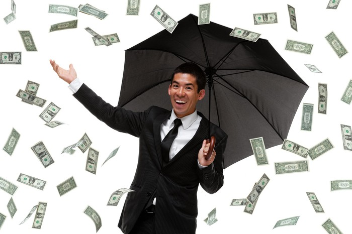 Money is raining down on a person in a suit holding an umbrella.