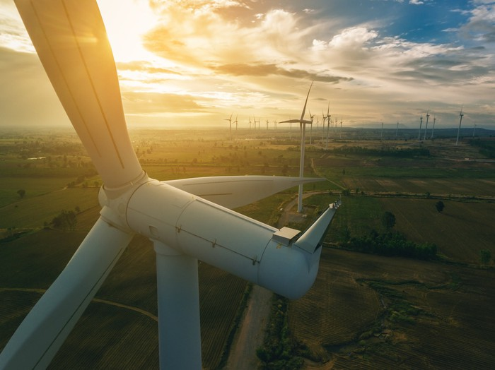 A wind turbine with the sun shining brightly.