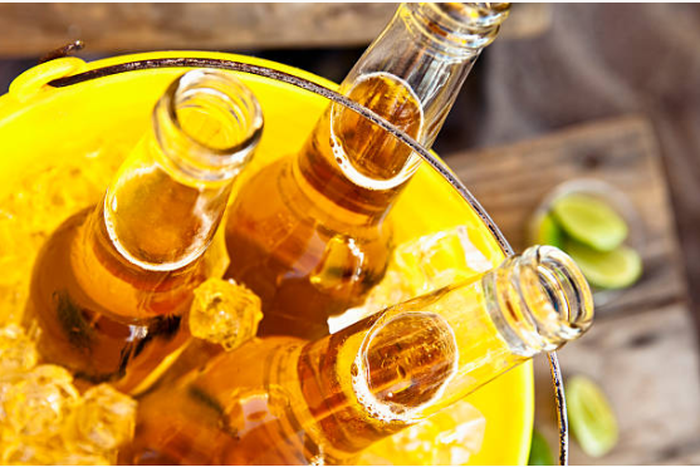 A metal bucket filled with ice and three open glass bottles of beer. The bucket sits on a wooden table scattered with pieces of lime.