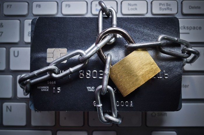 Credit card wrapped in chains with padlock