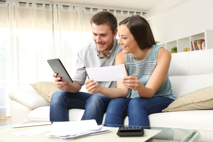 Man and woman seated on couch looking at a tablet with a stack of paperwork on the table in front of them