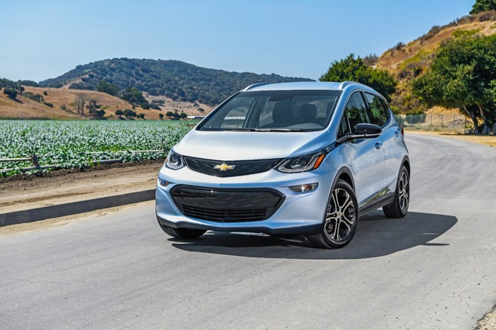 A silver 2018 Chevy Bolt EV drives on a road with mountains in the background