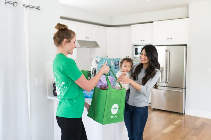 A Shipt shopper delivers same-day groceries at a customer's home
