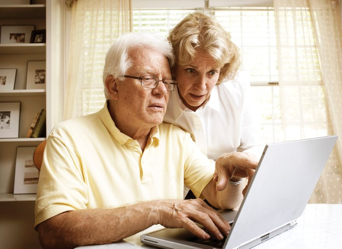 A senior couple examining their finances on their laptop.
