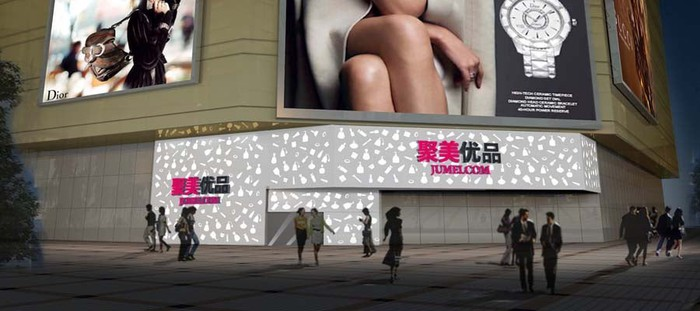 A city street corner, featuring large billboards and several marquees with Jumei's name and logo.