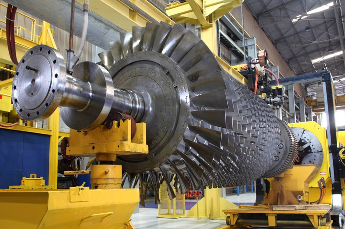 An industrial turbine sits in a factory.