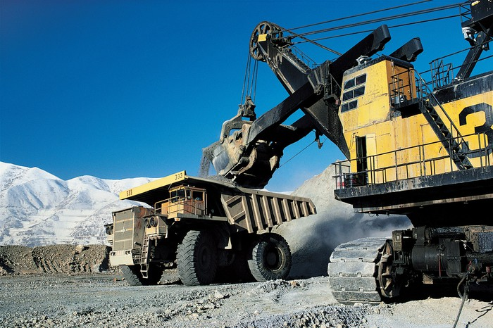 A coal excavator loading a dump truck in an open-pit mine.