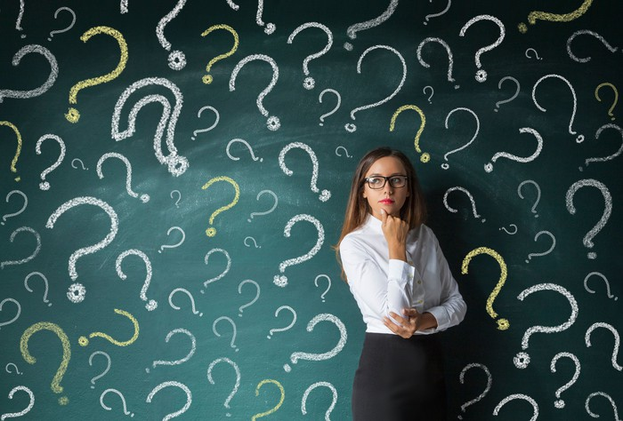 A businesswoman standing in front of a chalkboard with many question marks drawn on it.